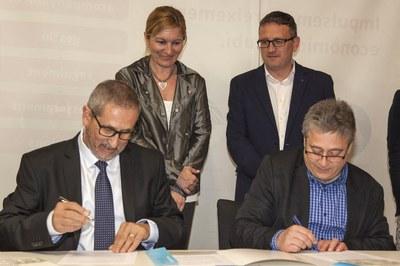 Manel Jiménez i Miquel Ortuño durant la signatura del conveni amb la presència de  l'alcaldessa i el regidor de comerç (foto: Localpres).