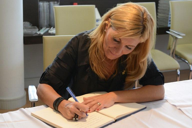 L'alcaldessa signant el llibre d'honor de Deltalab (foto: Localpres)