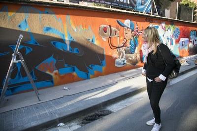 L'alcaldessa, observant l'evolució del grafit que decora des de dissabte una de les parets de la Torre Bassas (foto: Ajuntament – Lali Puig).
