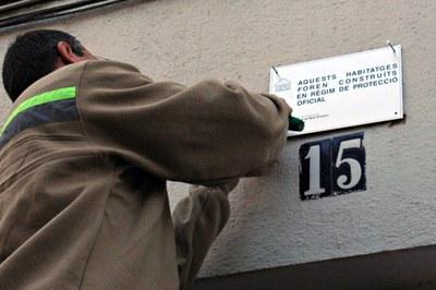 Las placas se sustituyen por otras donde se informa que el edificio fue construido en régimen de protección oficial (foto: Ayuntamiento de Rubí).