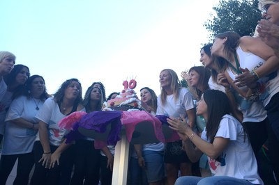 La alcaldesa y la concejala acompañante parte de la comunidad educativa de la Luna en el momento de soplar las velas del pastel.