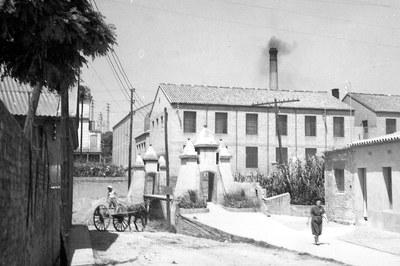 Vista del Vapor Nou con el puente colgante en primer término (foto: Josep Pallarols i Serra. Archivo Municipal).