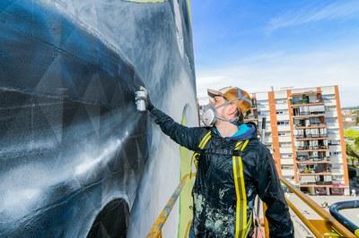 Urih en el proceso de pintar el mural.